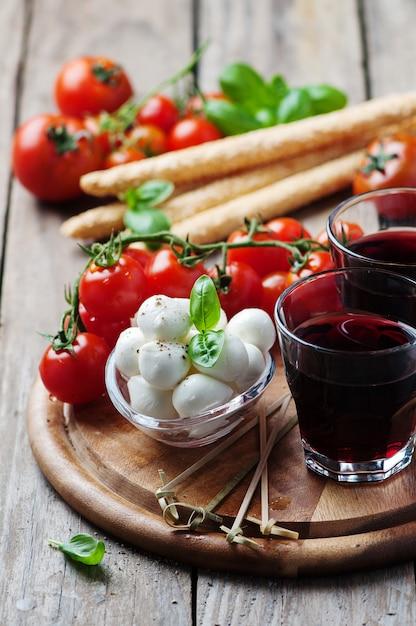Mozzarella, pomodoro e basilico sulla tavola di legno Foto Premium