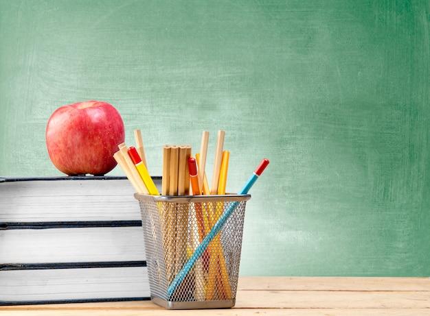 Mucchio dei libri con il contenitore di merce nel carrello delle matite e della mela sulla tavola di legno con la lavagna Foto Premium