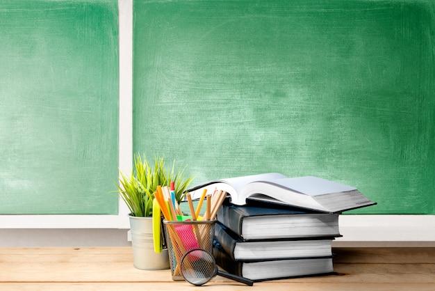 Mucchio dei libri con il contenitore di merce nel carrello delle matite e della pianta in vaso con la lente d'ingrandimento sulla tavola di legno Foto Premium
