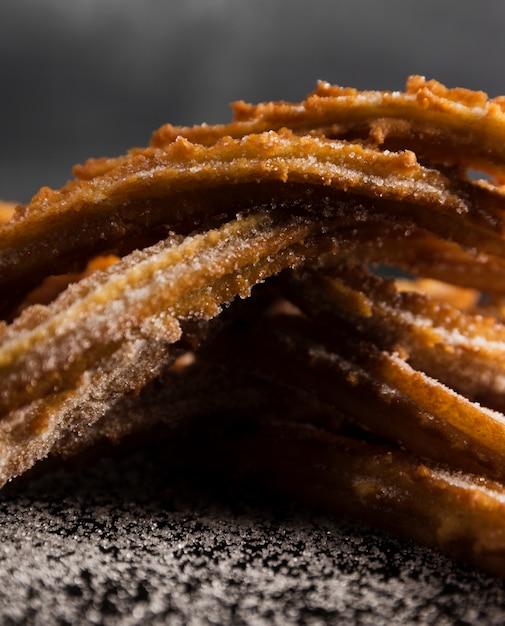 Mucchio del primo piano di churros e di zucchero fritti Foto Gratuite