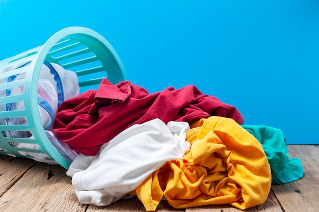 Mucchio della lavanderia sporca nel canestro di lavaggio su di legno Foto Premium