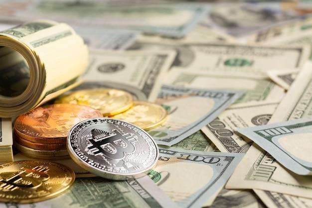 Mucchio di bitcoin in cima alle banconote in dollari Foto Gratuite
