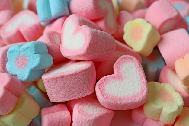Mucchio di caramelle marshmallow a forma di fiore rosa e bianco a forma di cuore e colore pastello Foto Premium