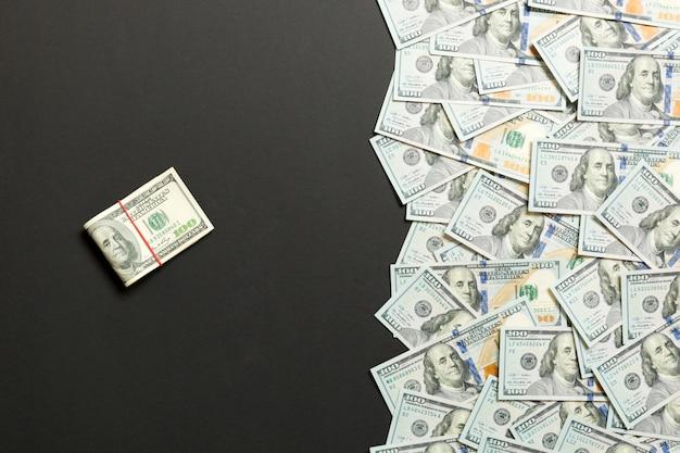 Mucchio di cento banconote in dollari su sfondo colorato Foto Premium