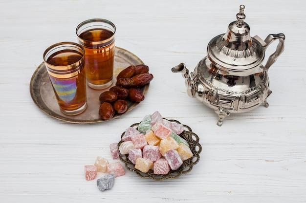 Mucchio di datteri secchi vicino a tazze di tè, delizie turche e teiera Foto Gratuite