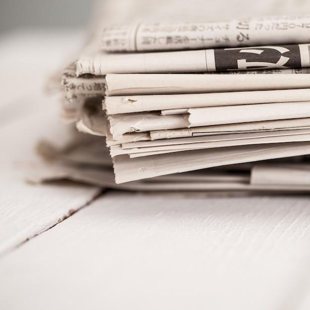 Mucchio di giornali su un tavolo bianco Foto Gratuite