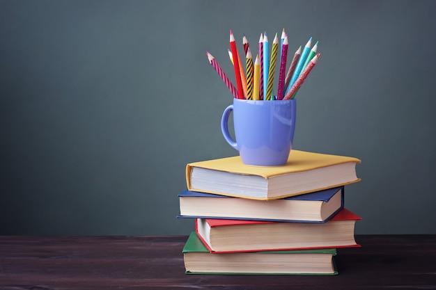 Mucchio di libri con copertine di colore e matite colorate in una tazza su un tavolo di legno. una natura morta con libri. Foto Premium
