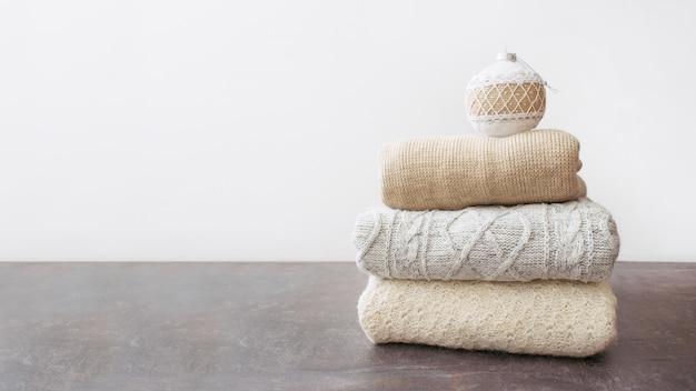 Mucchio di maglioni a maglia caldi con ornamento di natale e pupazzo di neve giocattolo Foto Premium