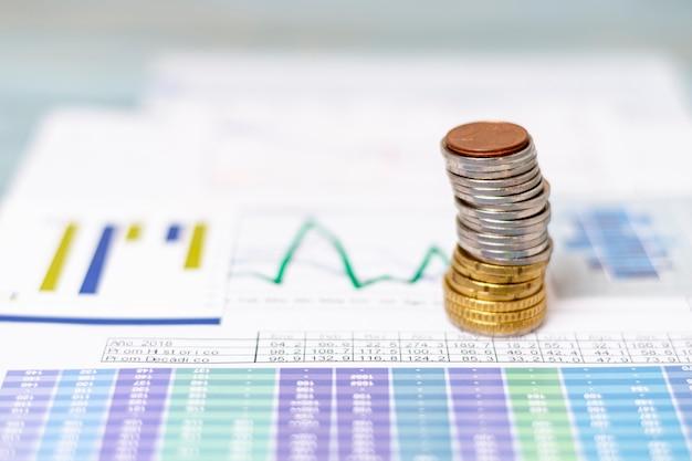 Mucchio di monete su diagrammi statistici Foto Gratuite