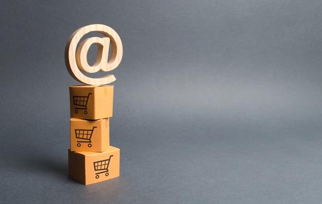 Mucchio di scatole di cartone con disegno di carrelli della spesa ed e-mail simbolo commerciale at Foto Premium