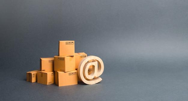 Mucchio di scatole di cartone e simbolo commerciale at. acquisti online. e-commerce. vendite di merci Foto Premium