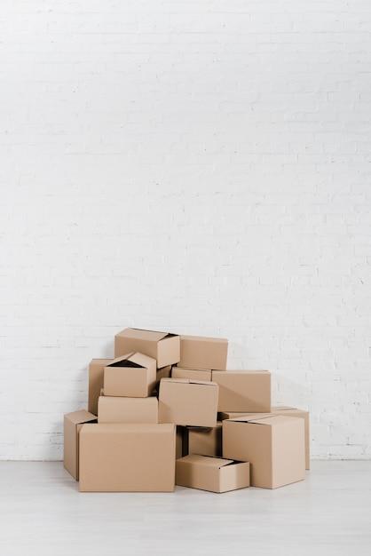 Mucchio di scatole di cartone impilate sul pavimento contro il muro bianco Foto Gratuite