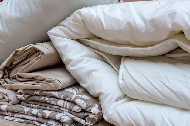 Mucchio impacchettato bianco e beige della coperta di lenzuola con cuscino e lenzuola Foto Premium