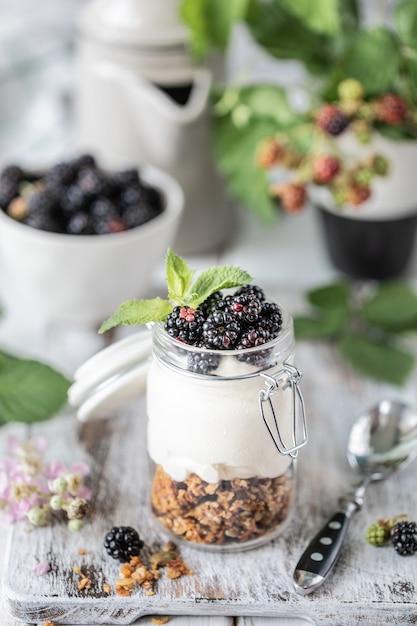 Muesli fatto a mano con yogurt bianco naturale con more in un barattolo di vetro trasparente Foto Premium
