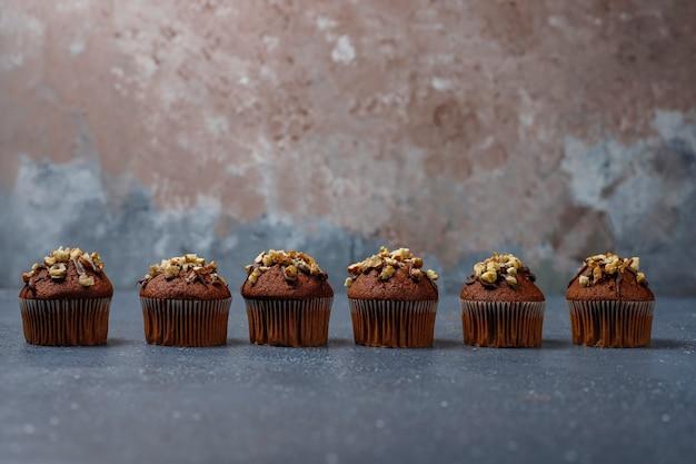 Muffin al cioccolato e noci con una tazza di caffè con noci sulla superficie scura Foto Gratuite
