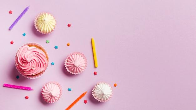 Muffin; candele; aalaw e spruzza su sfondo rosa Foto Gratuite