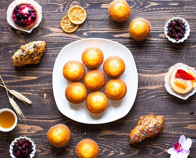 Muffin casalinghi deliziosi con yogurt, su una tavola di legno Foto Premium