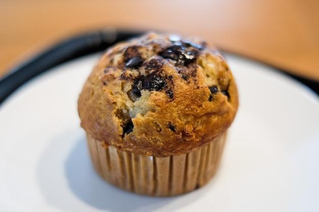 Muffin cioccolato lava con gocce di cioccolato e banana in tazza di carta per dessert. Foto Premium