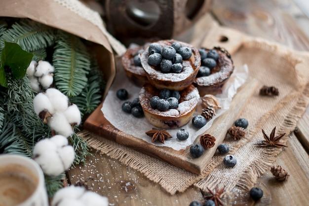 Muffin con mirtilli su un legno, bouquet di rami Foto Premium
