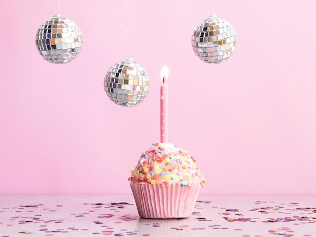 Muffin di compleanno delizioso con globi da discoteca Foto Gratuite