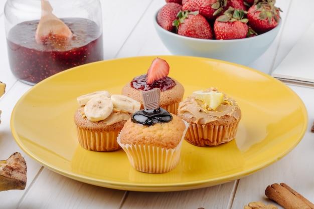 Muffin di vista laterale con le fragole delle banane cioccolato e limone su un piatto giallo Foto Gratuite