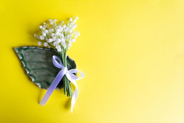 Mughetti legati con nastro su giallo. copia . fiori di primavera Foto Premium
