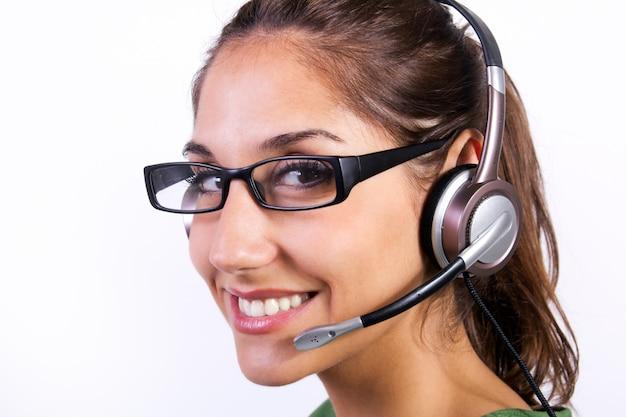 Mujer con auriculares en un centro de llamadas Foto Gratuite