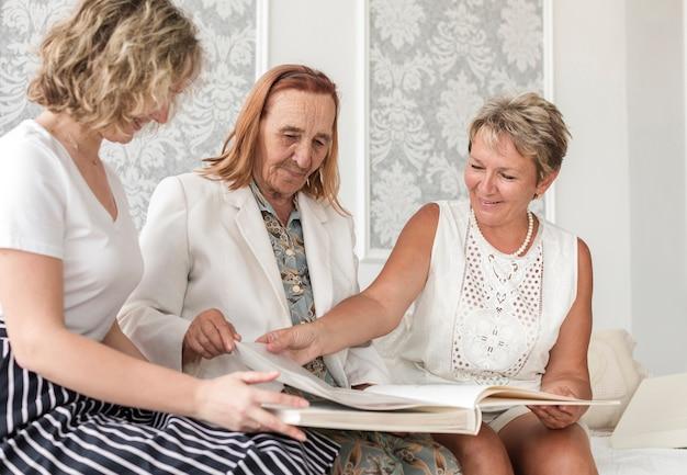 Multi donne della generazione che sembrano il vecchio album di foto durante la seduta sul sofà Foto Gratuite