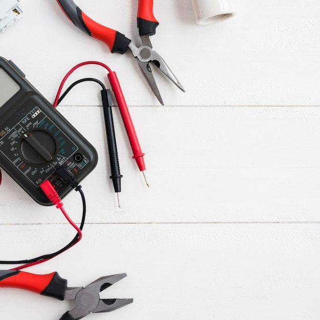 Multimetro digitale con tester e pinze sul tavolo di legno bianco Foto Gratuite