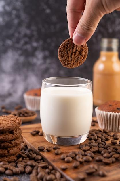 Munga in un bicchiere, completo di chicchi di caffè, cupcakes, banane e biscotti su un piatto di legno. Foto Gratuite