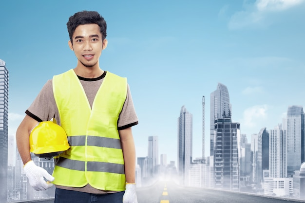 Muratore asiatico attraente che tiene casco giallo Foto Premium