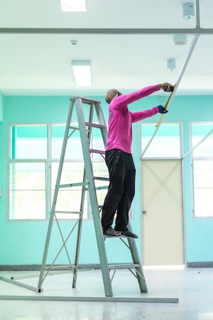 Muratore che sta sulle scale o sulla scala di alluminio facendo uso di un nastro di misurazione. Foto Premium