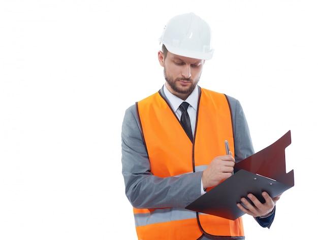 Muratore maschio che indossa giubbotto di sicurezza fluorescente e un elmetto protettivo che fa le note sui suoi appunti isolati sul bianco Foto Gratuite