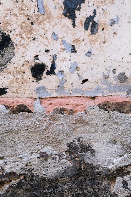 Muro di cemento con mattoni e macchie di sporco Foto Gratuite