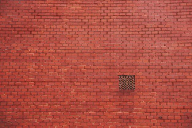 Muro di mattoni rossi con uno sfiato quadrato Foto Gratuite