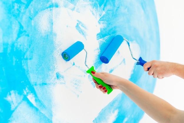 Muro dipinto di colore blu con rullo in mano. Foto Premium