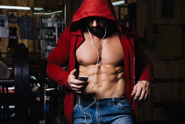 Muscolare in cappuccio con le cuffie Foto Gratuite