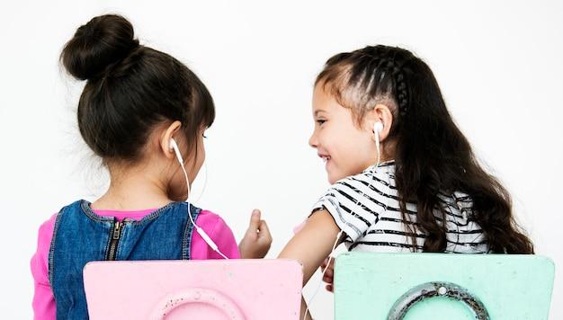 Musica d'ascolto degli amici di ragazze che si siedono sul fondo bianco Foto Premium