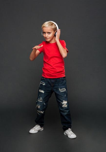 Musica d'ascolto del bambino emozionale del ragazzino con ballare delle cuffie. Foto Gratuite