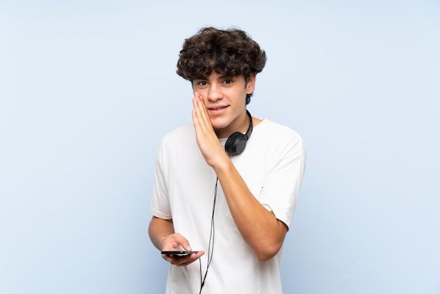 Musica d'ascolto del giovane con un cellulare sopra la parete blu isolata che bisbiglia qualcosa Foto Premium