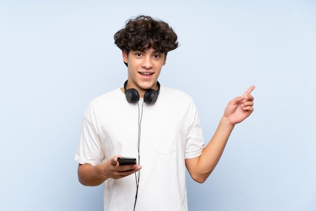 Musica d'ascolto del giovane con un cellulare sopra la parete blu isolata sorpresa e puntando il dito al lato Foto Premium