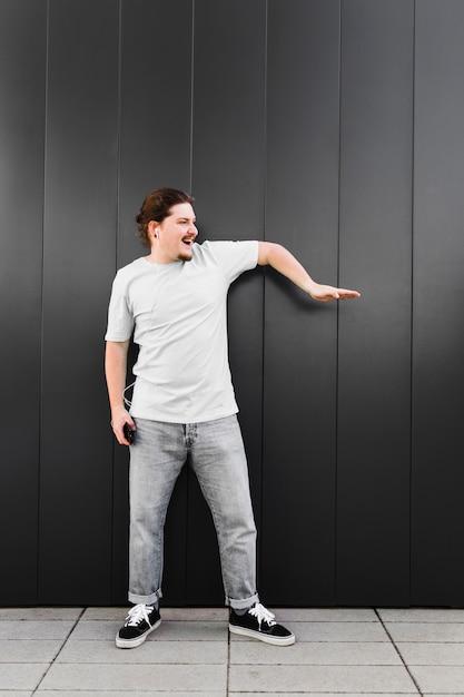 Musica d'ascolto del giovane sul trasduttore auricolare tramite dancing del telefono cellulare Foto Gratuite