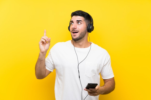 Musica d'ascolto del giovane uomo bello con un cellulare sopra la parete gialla isolata che intende realizzare la soluzione Foto Premium