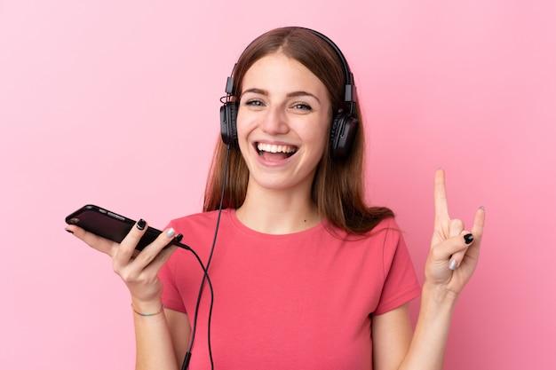 Musica d'ascolto dell'uomo sopra la parete rosa isolata Foto Premium