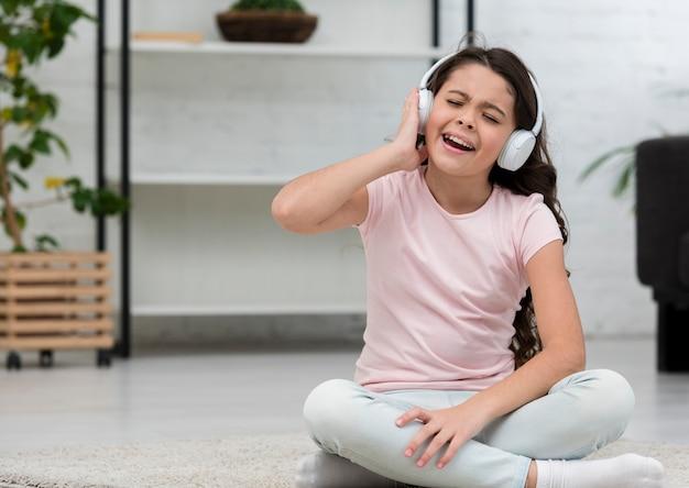 Musica d'ascolto della bambina tramite le cuffie all'interno Foto Gratuite