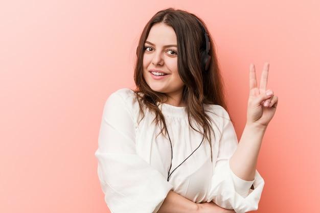 Musica d'ascolto della donna curvy di dimensione più giovani con le cuffie che mostrano numero due con le dita. Foto Premium