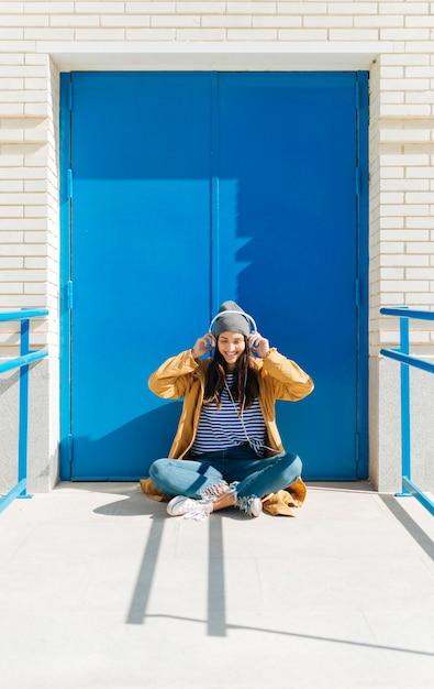 Musica d'ascolto della donna felice sullo smart phone che si siede contro la porta blu all'aperto Foto Gratuite