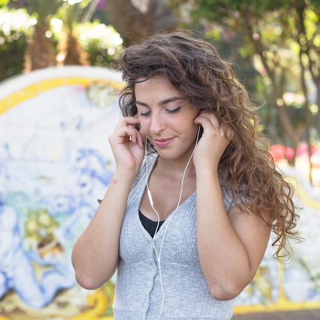 Musica d'ascolto della donna moderna nel parco Foto Gratuite