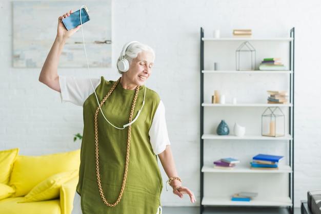 Musica d'ascolto della donna senior sul dancing della cuffia nel salone Foto Gratuite