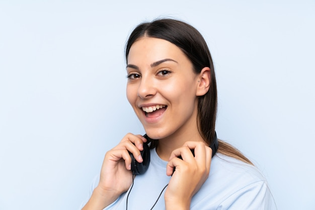 Musica d'ascolto della giovane donna sopra la parete blu isolata Foto Premium